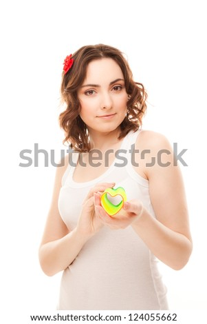 Beautiful woman with heart shaped toy isolated on white