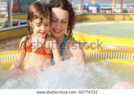 beautiful woman with her daughter is relaxing in hot tub on cruise ship. - stock photo