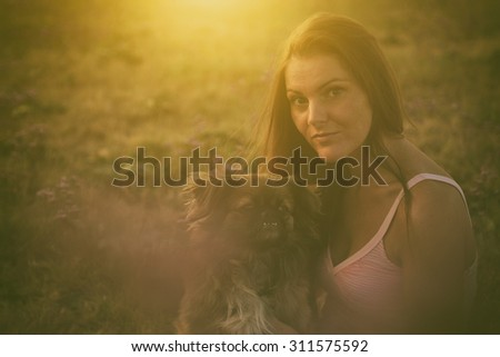 Beautiful woman with her dog in the nature