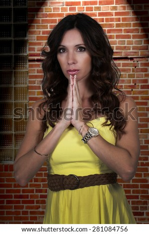 Beautiful woman with her hands clasped in despair - stock photo