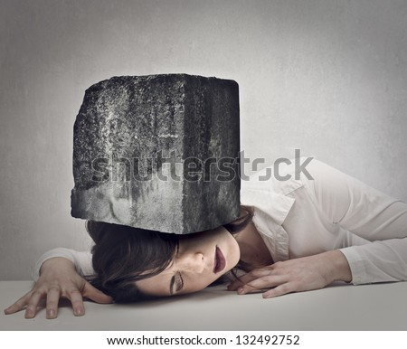 beautiful woman with her head crushed by a huge boulder - stock photo