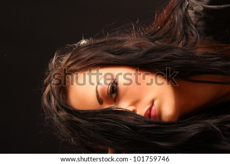 Beautiful woman with her long black hair covering half of her face - stock photo