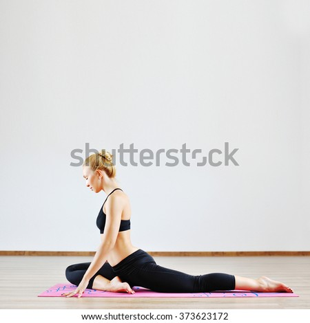 Beautiful woman with high body flexibility exercising in the gym - stock photo