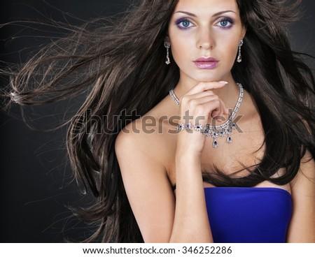 Beautiful woman with jewellery on dark background - stock photo