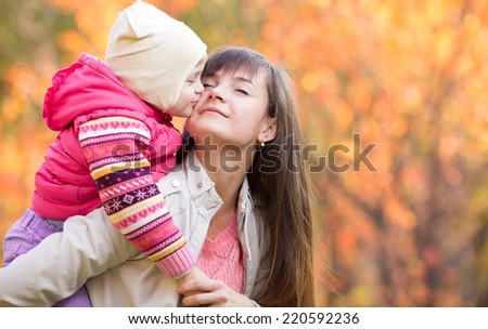 Beautiful woman with kid girl outdoors in fall. Child kissing mom. Mothers day holiday concept. - stock photo