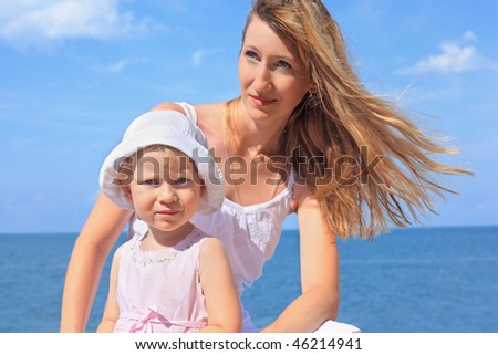 beautiful woman with little girl in white hat near sea - stock photo