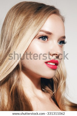 Beautiful woman with long blond curly hair. Portrait of fashion model with bright makeup.