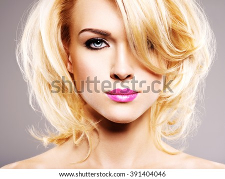 Beautiful woman with long blond curly hair. Portrait of fashion model with bright makeup.  - stock photo