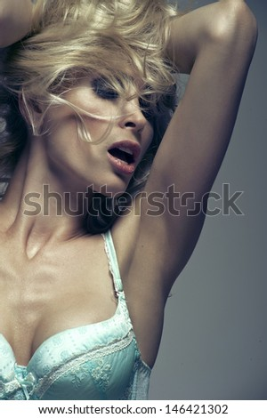 Beautiful woman with long blond hair. Closeup portrait of a fashion model posing at studio.  - stock photo