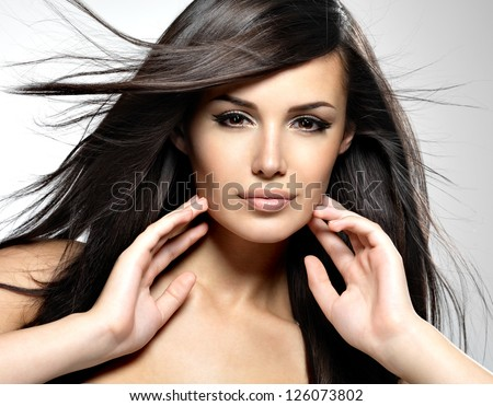 Beautiful woman with long brown hair. Closeup portrait of a fashion model posing at studio. - stock photo