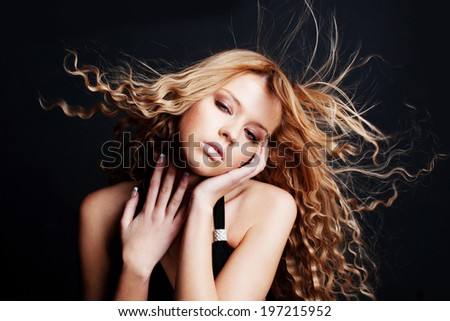 Beautiful woman with long curly blond hair. Fashion model posing at studio.