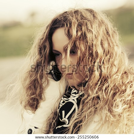 Beautiful woman with long curly hairs calling on mobile phone - stock photo