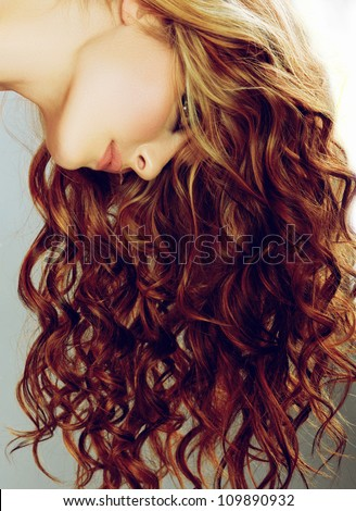 beautiful woman with long curly red hair on studio background - stock photo
