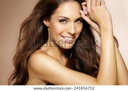 Beautiful woman with long dark hair posing on beige background.