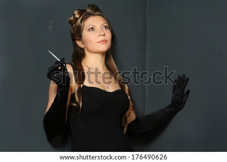 beautiful woman with long hair in black dress and gloves smoking cigarette - stock photo
