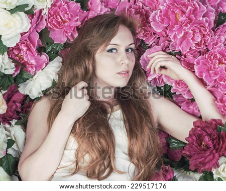 Beautiful Woman with Long Hair on the Background of Peony Flowers