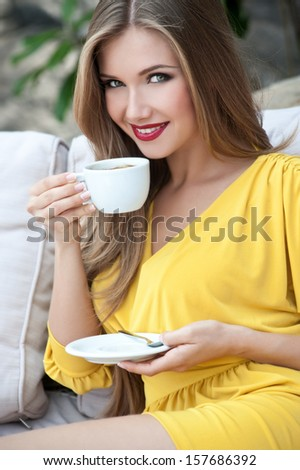 Beautiful woman with long hair sitting on sofa in the street cafe and drinking coffee - stock photo