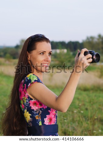 Beautiful woman with long hair taking pictures of a landscape on a summer evening - stock photo