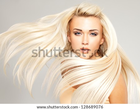 Beautiful woman with long straight blond hair. Fashion model posing at studio. - stock photo