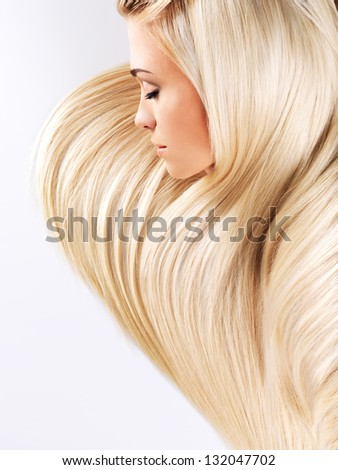 Beautiful woman with long straight blond hairs. Fashion model posing at studio.