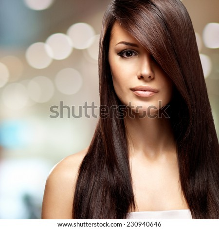 Beautiful woman with long straight brown hair. Fashion model posing at studio over art creative background - stock photo