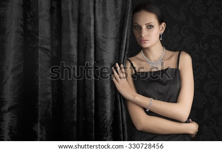Beautiful woman with luxury jewellery on dark background. Space for text.
