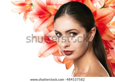 Beautiful woman with makeup on face and flowers background. Beauty concept.