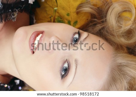 beautiful woman with maple leaves studio shot