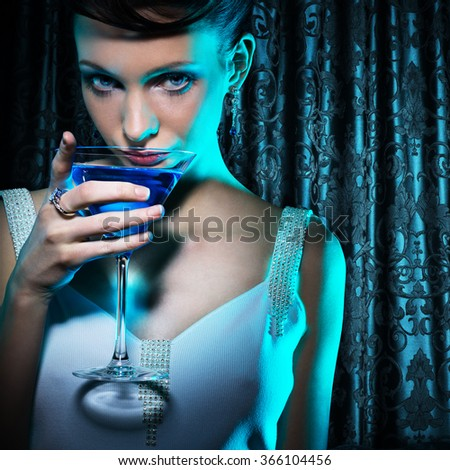 Beautiful woman with martini glass on damask curtain background - stock photo