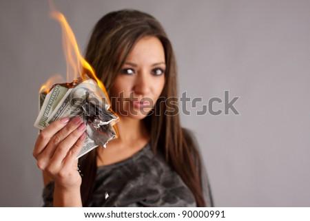 Beautiful woman with money to burn. - stock photo