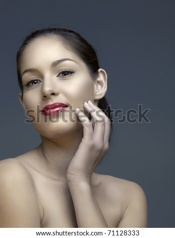 beautiful woman with natural make-up and long lashes touching her face with a soft smile - stock photo