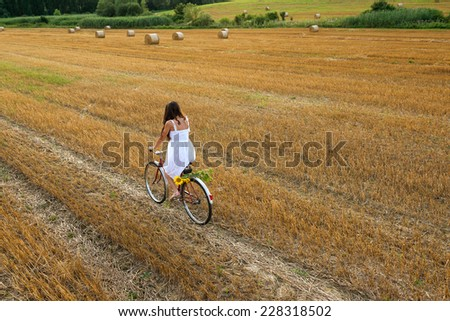 Beautiful woman with old bike in the wheat field - stock photo