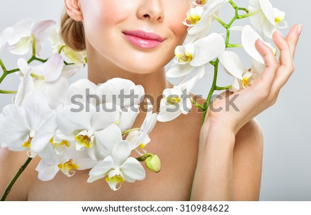 Beautiful woman with Orchid Flowers. Perfect Skin. Professional Makeup. Skincare concept. - stock photo