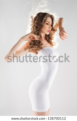 beautiful woman with perfect body dressed in white modeling dress - stock photo