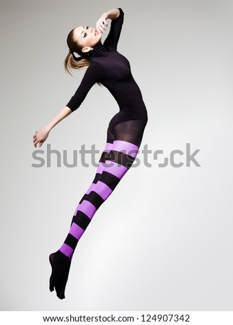 beautiful woman with perfect body jumping dressed in purple striped tights and black top - stock photo