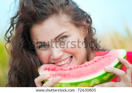 Beautiful woman with perfect hair and skin posing in wheat field and eating watermelon. Picnic.