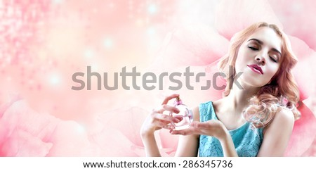 Beautiful woman with perfume bottle in flowers on pink background - stock photo