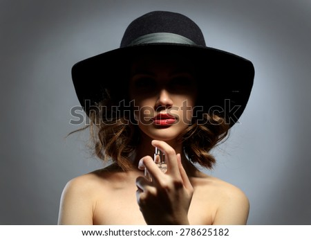 Beautiful woman with perfume bottle on gray background - stock photo