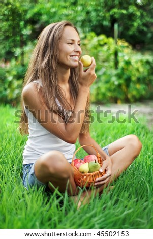 Beautiful woman with picnic crib eating pear on the green grass - stock photo