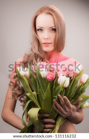 beautiful woman with pink and white tulips in studio