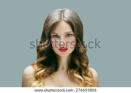 Beautiful woman with professional hair style and make up. Blond curly hair with ombre coloring, clean shiny skin. - stock photo