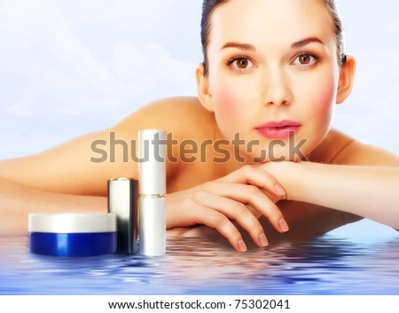 Beautiful woman with professional makeup lying on water surface with cosmetic products near by