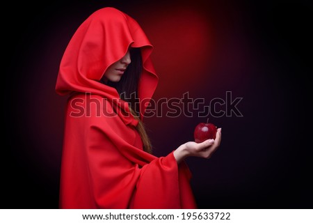 beautiful woman with red cloak holding apple in her hand - stock photo