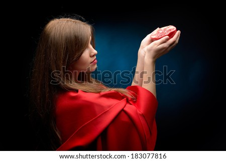 beautiful woman with red cloak holding pomegranate in studio