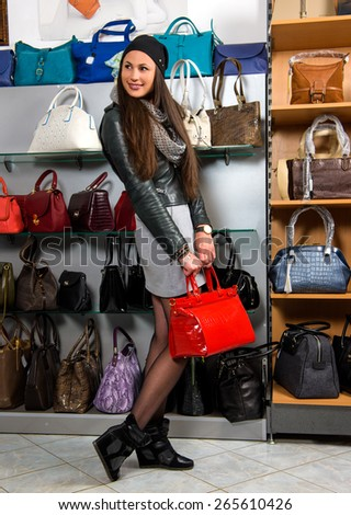 Beautiful woman with red  leather  bag in the store - stock photo