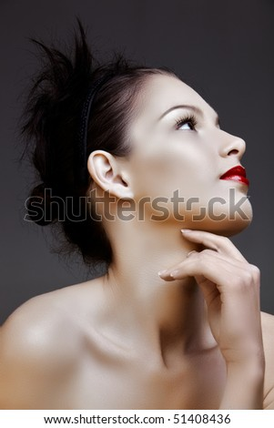 beautiful woman with red lips and hair in knot, resting on her hand - stock photo