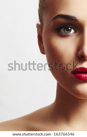 beautiful woman with red lips.close-up portrait. half face.unusual - stock photo