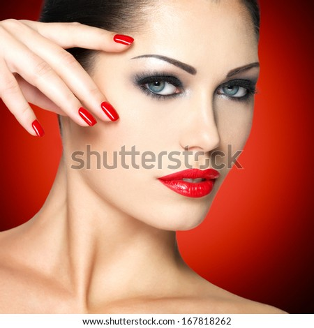 Beautiful woman with red nails and fashion makeup - stock photo