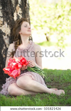 Beautiful woman with red spring tulips in a garden - stock photo