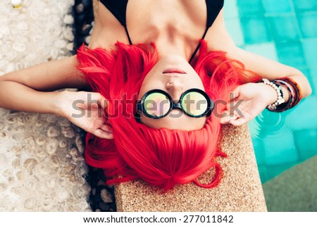 Beautiful woman with red wig hair in black bikini and sunglasses relaxing beside a swimming pool. Outdoors lifestyle portrait - stock photo